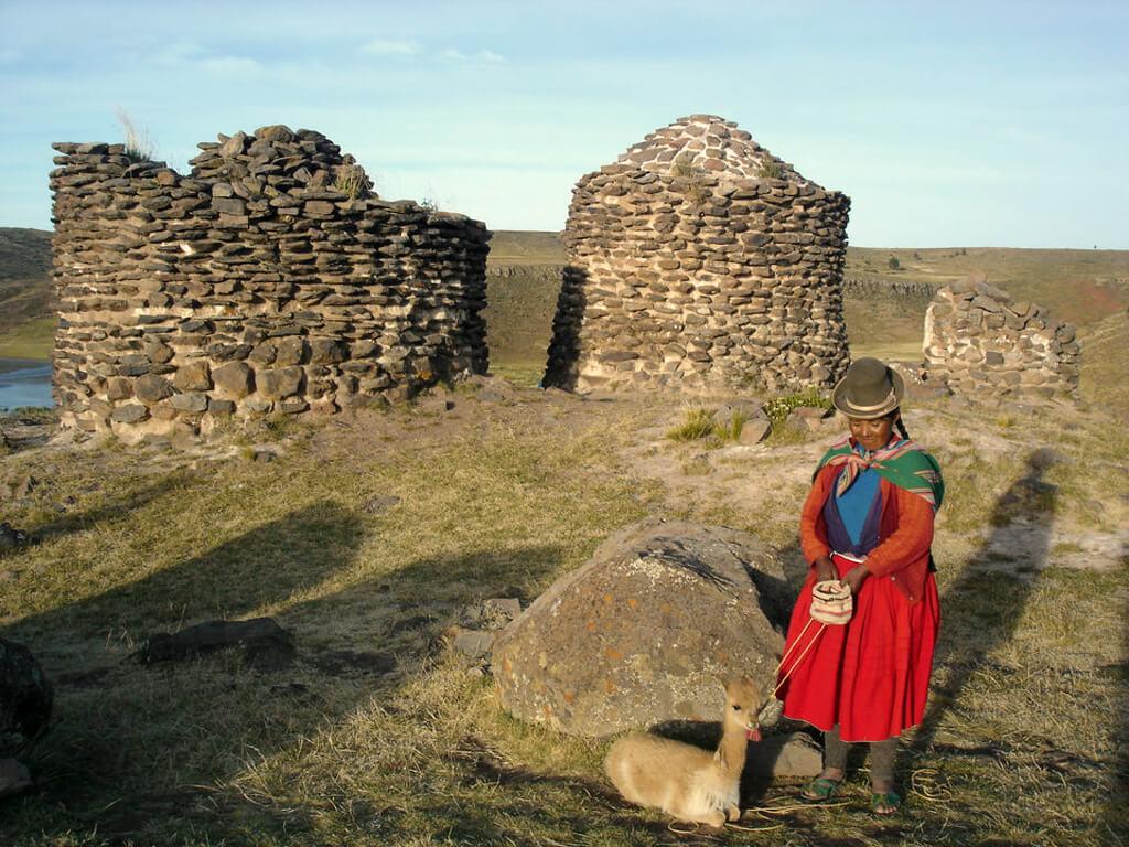 Femme Inca avec un bébé vigogne à côté des Chullpas au Pérou